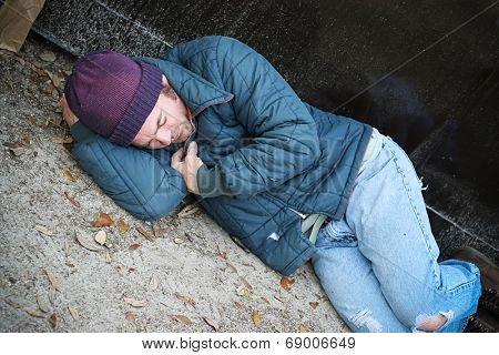 Homeless man cold and along trying to sleep on the ground beside a dumpster.