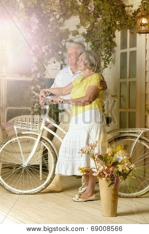Elderly couple with bicycle on veranda