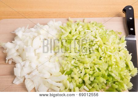 Chopped Onion And Celery With Knife On Cutting Board