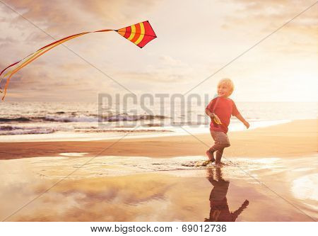 Happy young boy flying kite on the beach at sunset