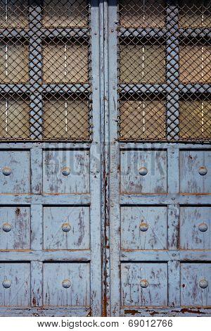 Old Door With Bars In Sunlight