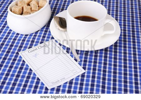 Check and cup of coffee on table close-up