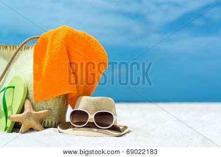 Summer beach bag with coral,towel and flip flops on sandy beach