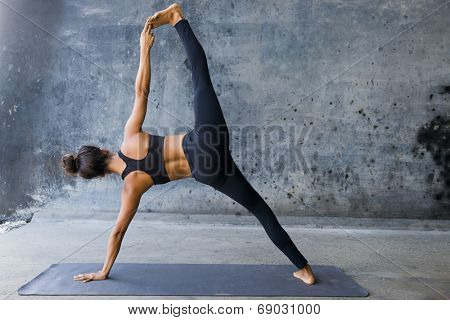 Woman practicing advanced yoga against a dark texturized wall