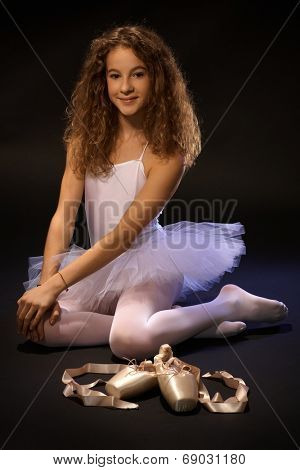 Pretty ballet student sitting on floor, smiling, looking at camera.