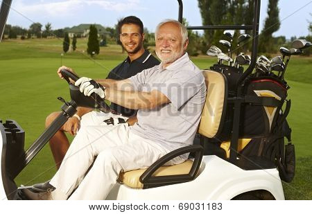 Happy golfers sitting in golf cart, smiling, looking at camera.