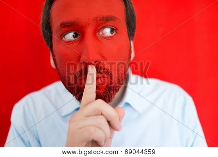 Portrait of adult man with red painted face asking for silence secret