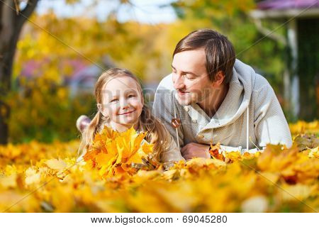 Father and his adorable little daughter outdoors on sunny autumn day laying on ground covered with fallen yellow leaves