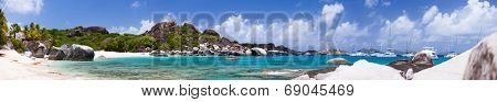 Panorama of a picture perfect beach with white sand, unique huge granite boulders, turquoise ocean water and blue sky at Virgin Gorda, British Virgin Islands in Caribbean