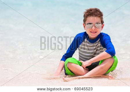 Cute little boy in sun protection rash guard at tropical beach on summer vacation