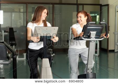 Two Happy Young Women In The Gym Biking