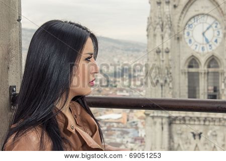 Girl in balcony with city view behind her