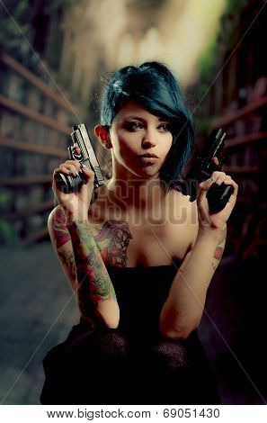 provocative tattooed girl holding gun