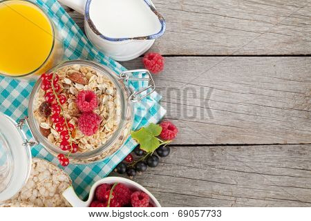 Healty breakfast with muesli, berries and orange juice. View from above on wooden table with copy space