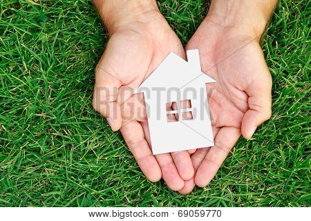 Hand Hold House Against Green Field
