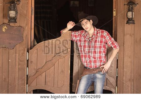 Cowboy in hat standing near saloon entrance