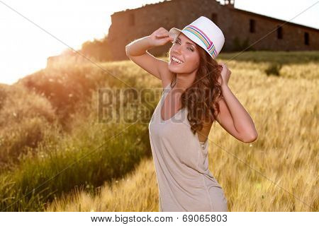 Portrait of a woman on golden cereal field in summer