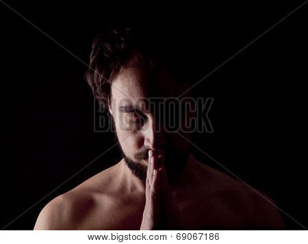 Low Key Image Of A Bearded Man Praying