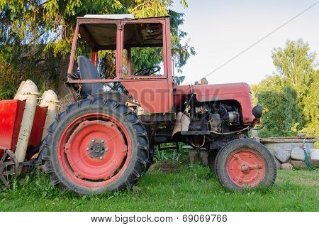 Close Up Of Rural Tractor With Red Wheel In Garden