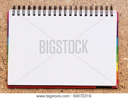 Blank notebook with spiral bind spine on a wood background