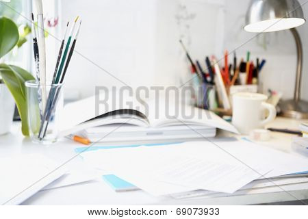 Artist's desk with books; papers and brushes