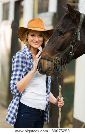 pretty cowgirl with her horse in stable
