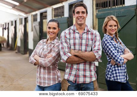 portrait of horse farm workers with arms crossed in stable