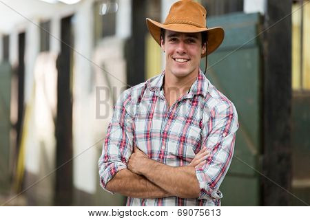 good looking cowboy with arms crossed in stable
