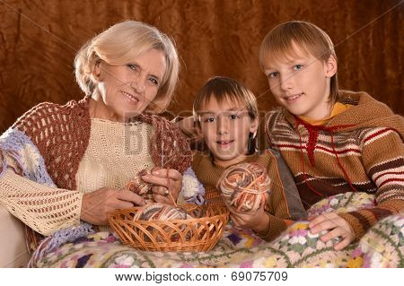 Senior woman knitting with grandsons