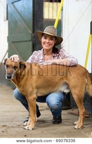 cheerful cowgirl and her dog inside farm house