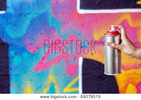 Vandalism, graffiti. Girl holding spray can