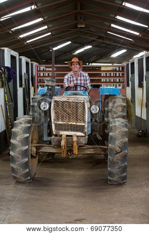 handsome cowboy driving tractor inside stables