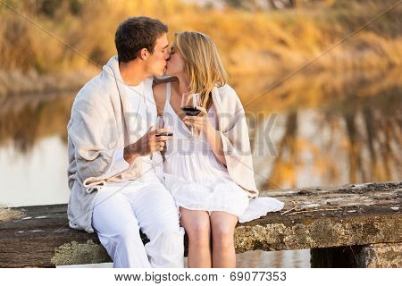 romantic couple kissing on a pier and holding glass of wine at sunset