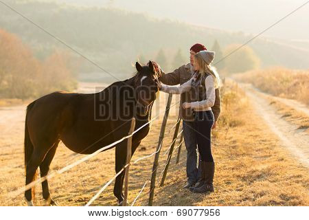 beautiful couple petting horse in the ranch