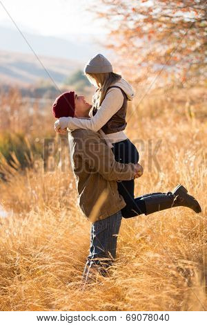 playful young man picking up his girlfriend by the lake in fall
