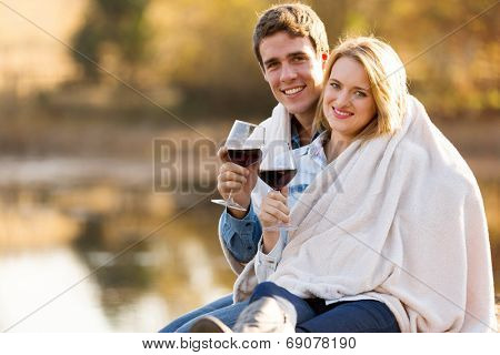 beautiful young couple snuggle outdoors with glass of wine