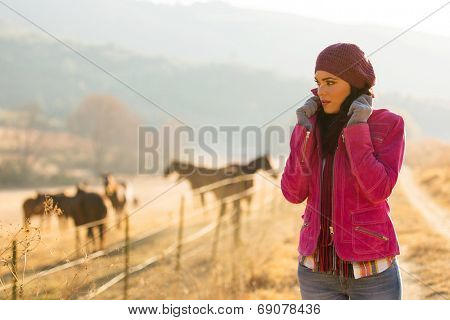 beautiful young woman at horse farm in the cold winter morning