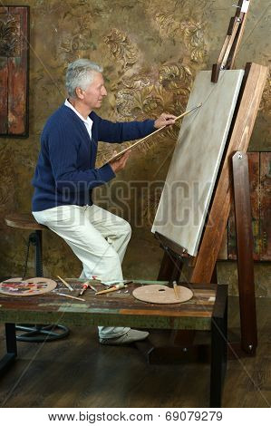 Elderly man painting with easel