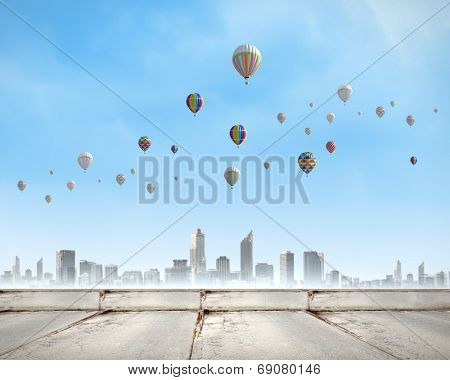 Colorful aerostats flying in clear sky above modern city