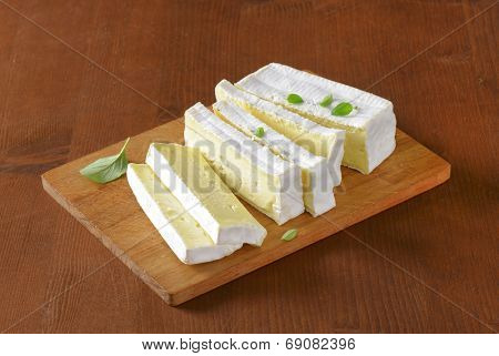 sliced block of surface ripened cow's milk cheese, served on the wooden cutting board
