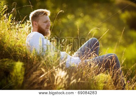 Happy Man On The Grass And Looks Into The Distance