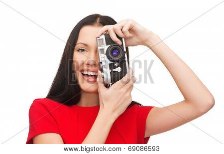 modern technology and people concept - smiling woman in casual clothes taking picture with vintage film camera
