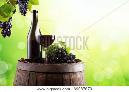 Wine still life on wooden keg with blur green abstract background
