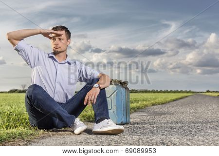 Full length of young man shielding eyes while sitting with petrol can by country road