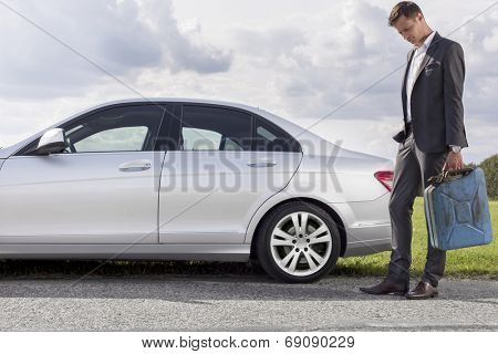 Full length of sad young businessman carrying gas can by broken down car at countryside
