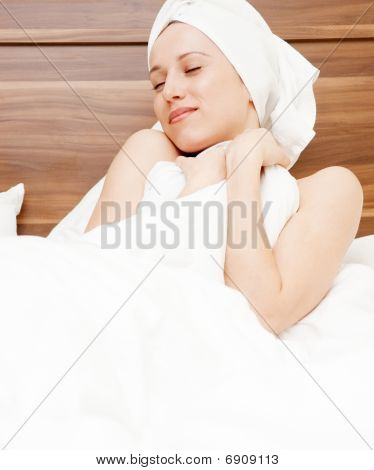 Young Woman Luxuriating In Soft Bed
