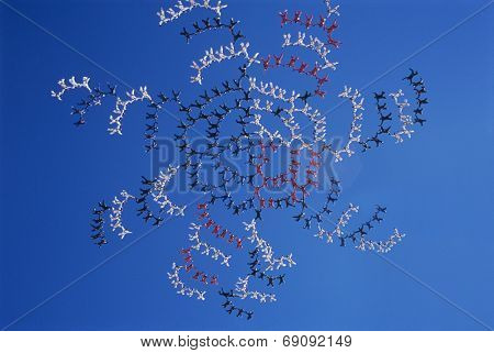 Large group of skydivers flying in formation of flower against blue sky
