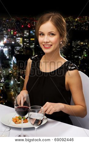 restaurant, people and holiday concept - smiling young woman eating main course at restaurant