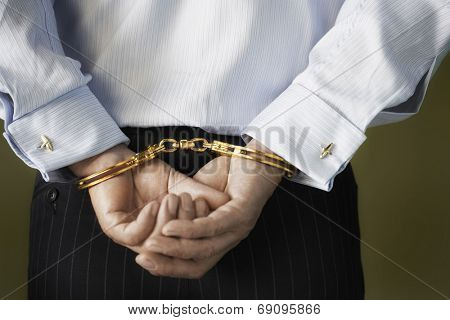 Closeup midsection of a businessman with hands cuffed behind back against green background