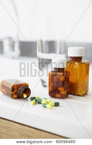 Spilt bottle of pills on counter in bathroom close up